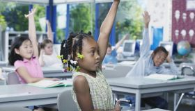 Young children sitting in a classroom at school with their hands raised