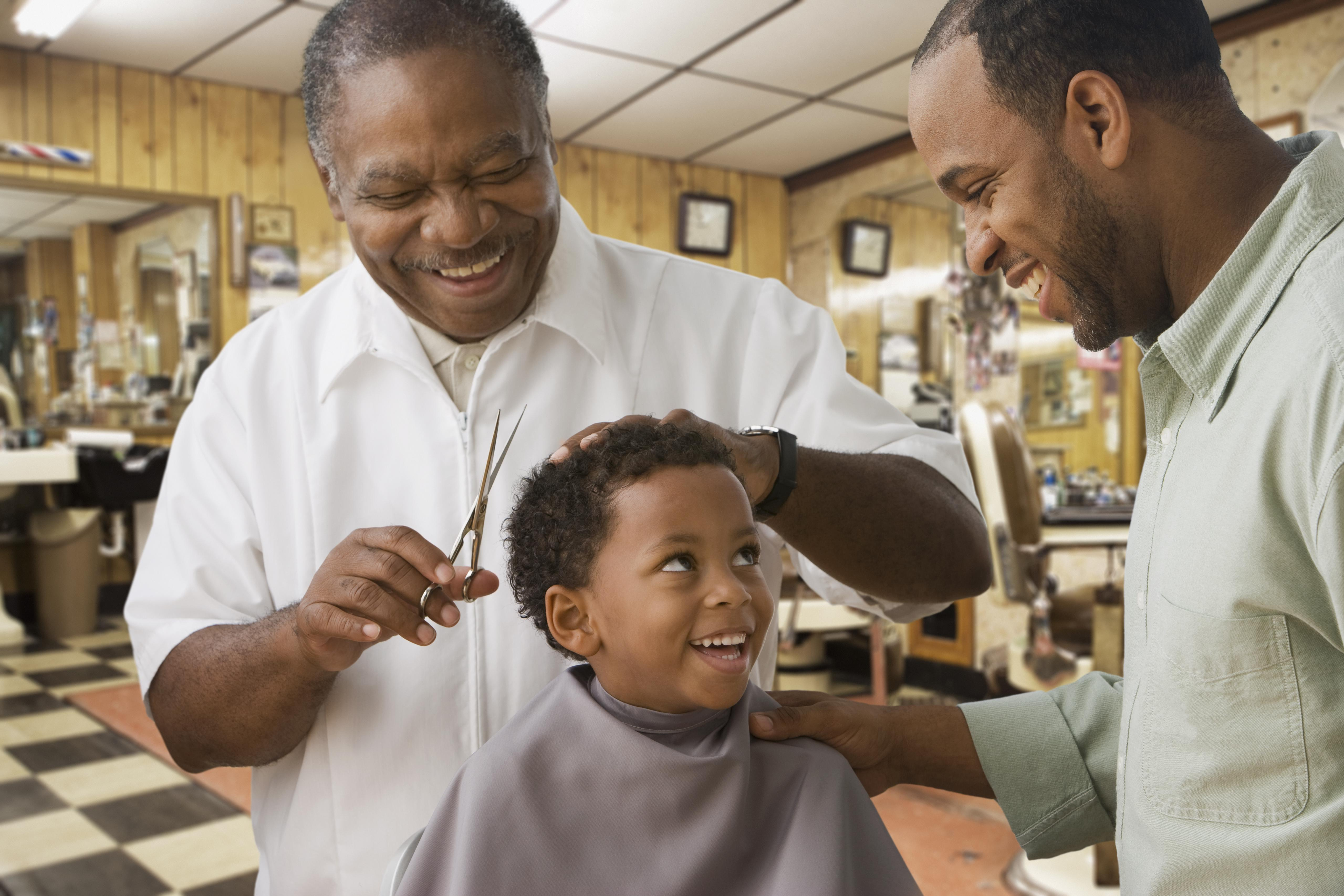 African boy with father getting haircut at barbershop