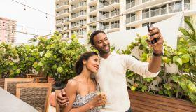 Couple taking selfie on urban rooftop