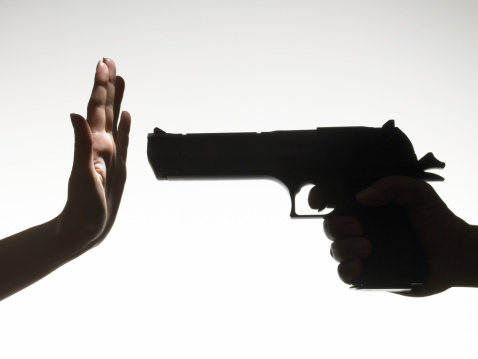 Man pointing gun at a woman making hand gesture close up