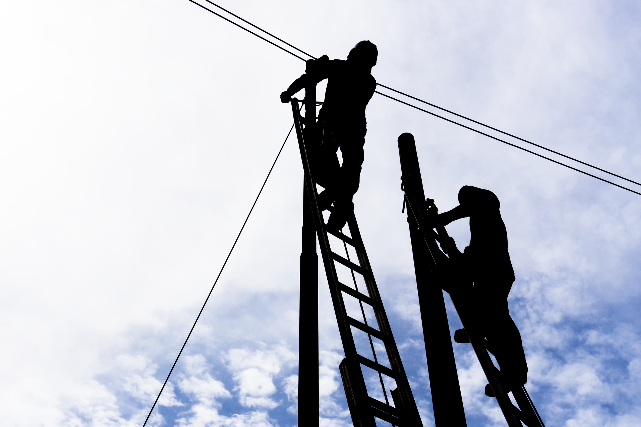 Silhouettes of Two Men Working on Electric Power Line Pole