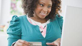 African American woman shopping online with credit card
