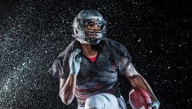 Water splashing on black football player running