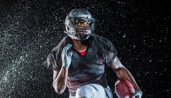 Water splashing on black football player running