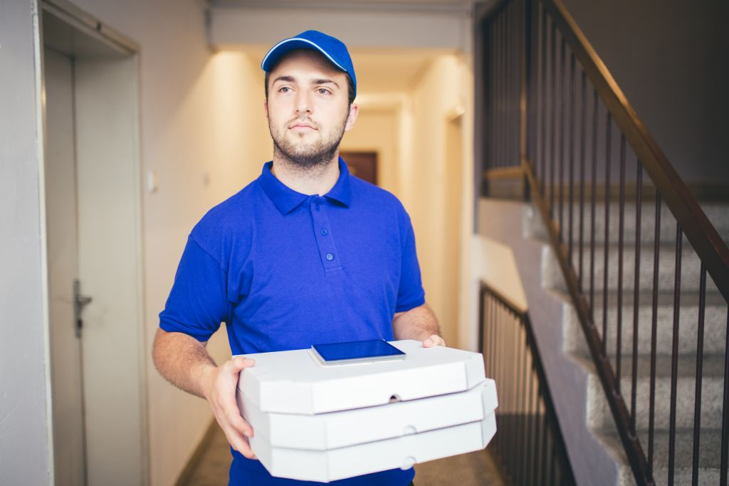 Delivery boy bringing pizza