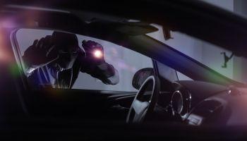 Close-Up Of Burglar Looking Into Car