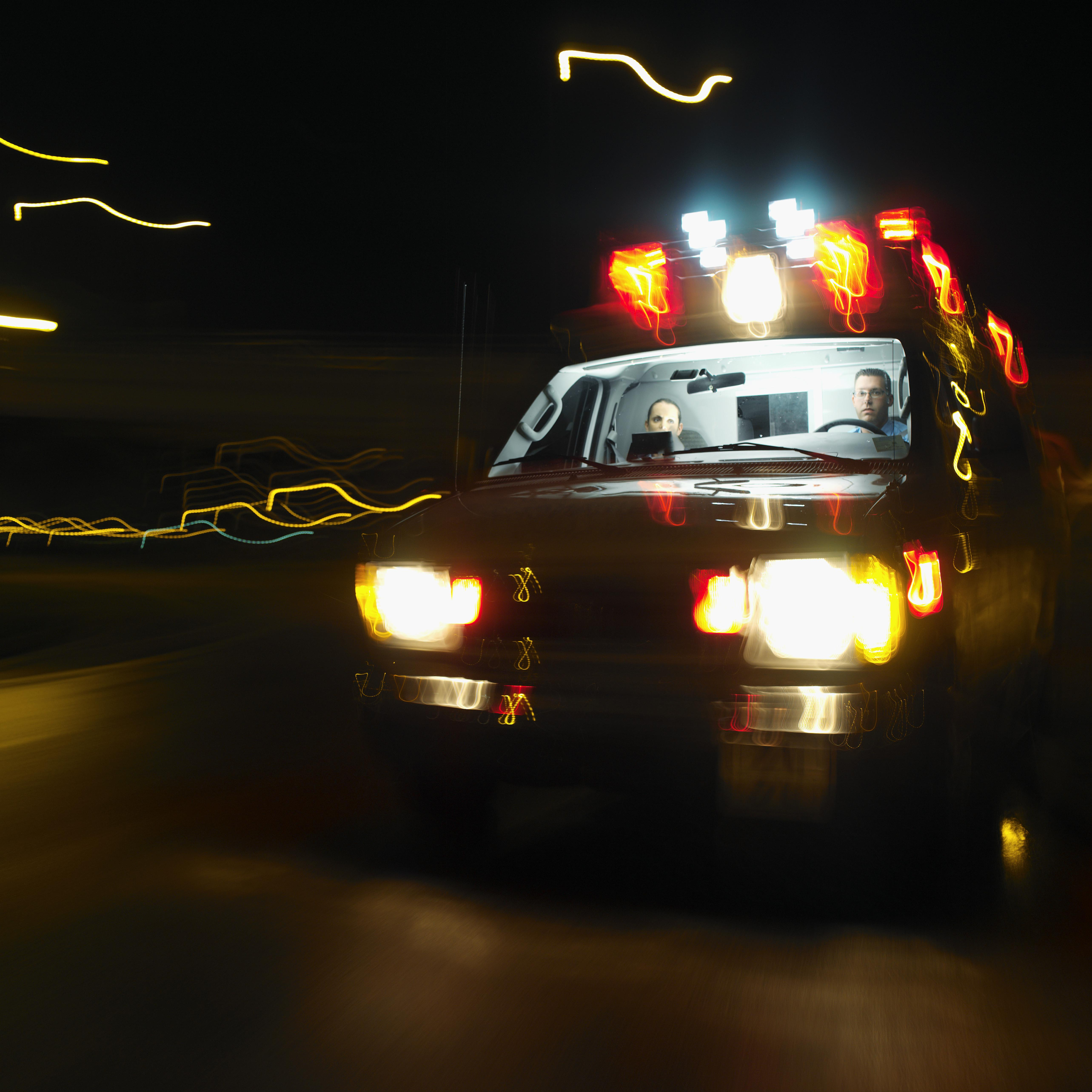 An ambulance on the road at night with two young paramedics inside (blurred)