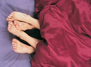 Couples Feet Together in Bed