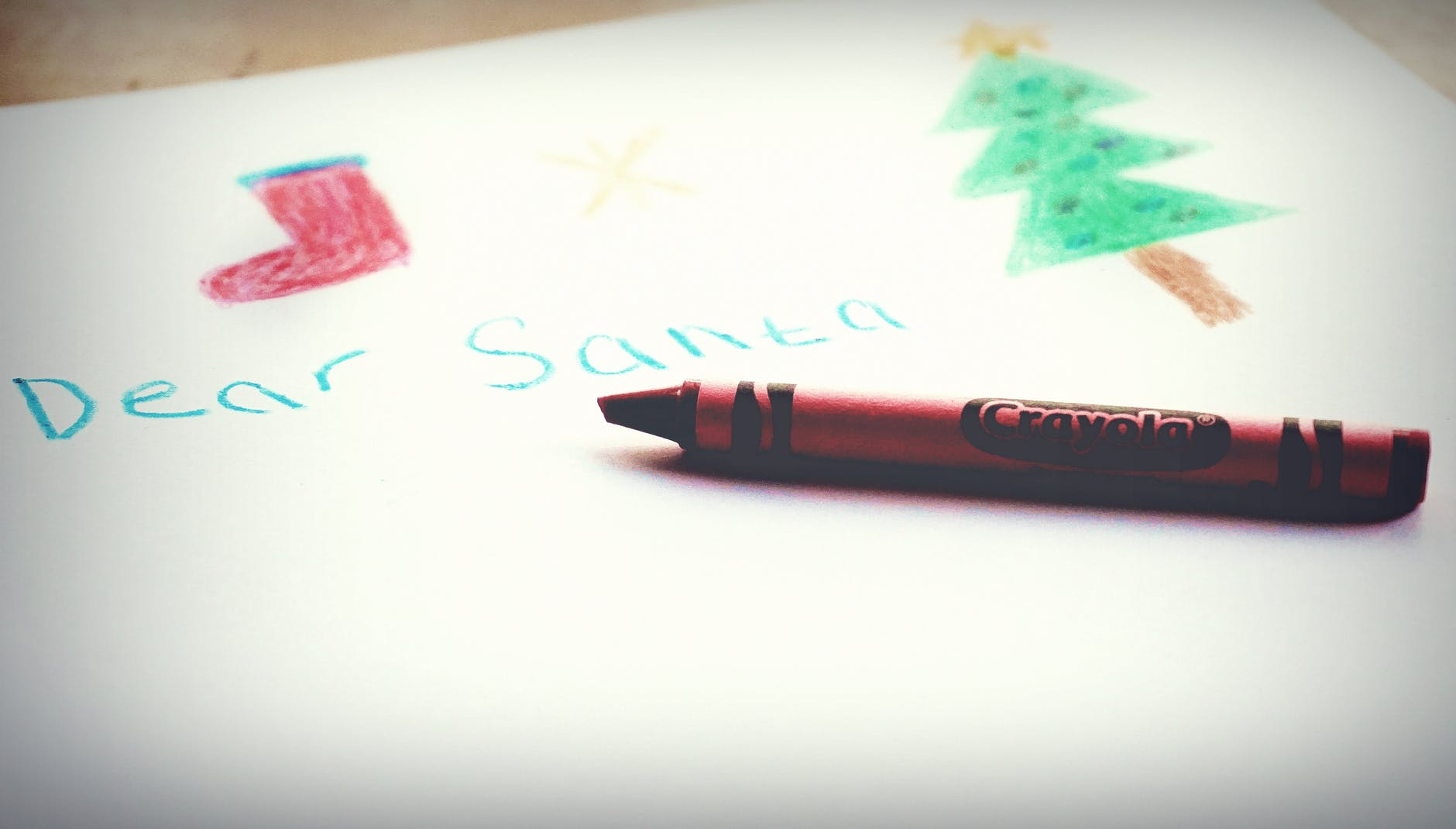 selective focus photography of red crayola crayon placed on white paper