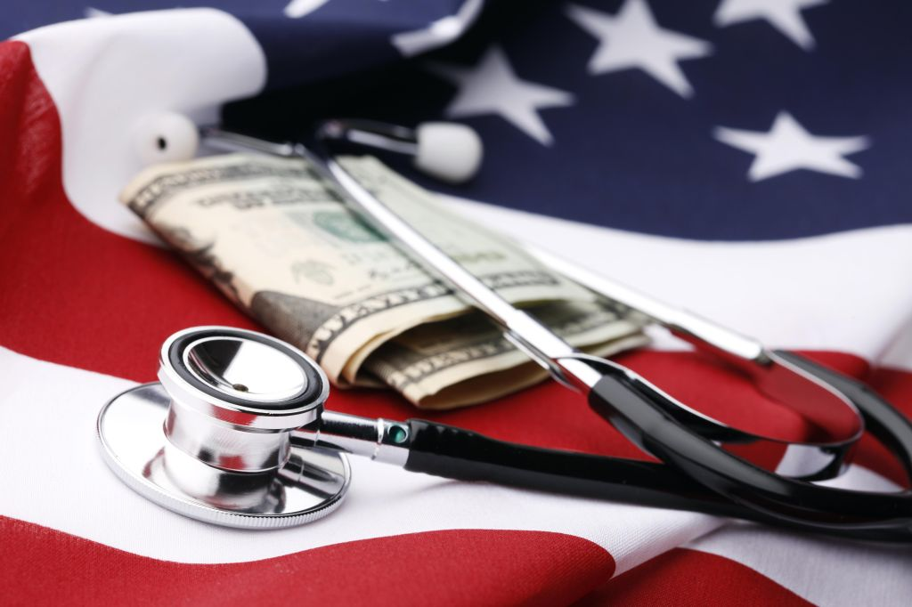 Stethoscope and U.S. cash over an American flag.