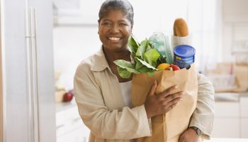 Middle-aged African woman holding a bag of groceries