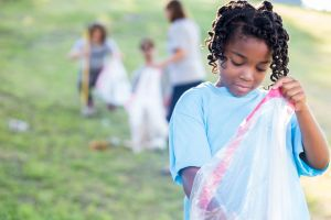 Helpful little girl volunteers with neighbors in community cleanup day
