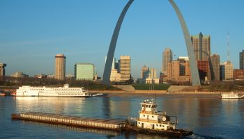 Tugboat pushing barge in front of Archway in St. Louis, Missouri