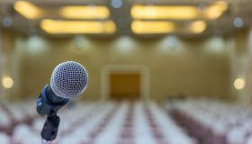 Close Up. Microphone In Conference Hall. Microphone Over The Abstract Blur Photo Of Seminar Room.