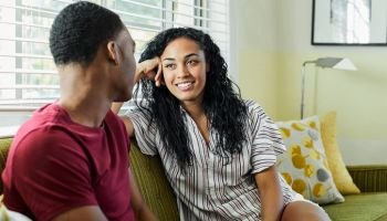 Smiling young woman relaxing with man at home